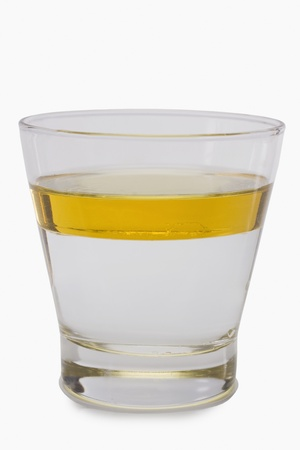 Oil floating on water surface in a glass Stock Photo