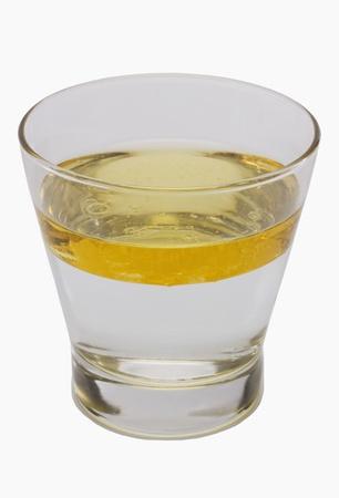 Olie drijvend op het water oppervlak in een glas
