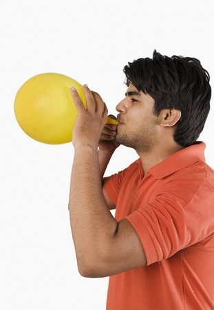 Man blowing up a balloon photo