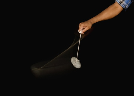 pendulum: Close-up of a persons hand swinging a stone pendulum