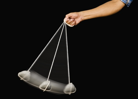 Close-up of a person's hand swinging a stone pendulum Stock Photo - 10241530