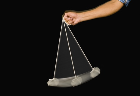 Close-up of a person's hand swinging a stone pendulum Stock Photo - 10235188