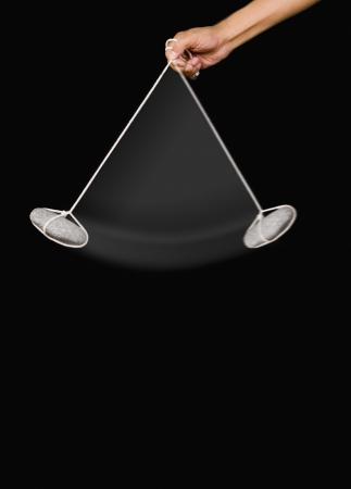 pendulum: Close-up of a persons hand swinging a stone pendulum