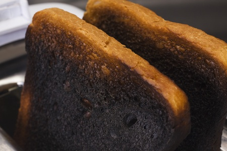 careless: Close-up of burnt toasts in a toaster Stock Photo