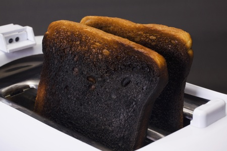 inconvenience: Close-up of burnt toasts in a toaster Stock Photo