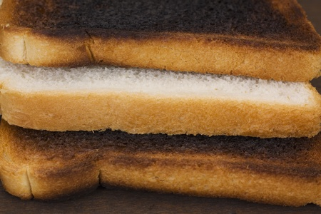 Slice of a bread between two burnt toasts