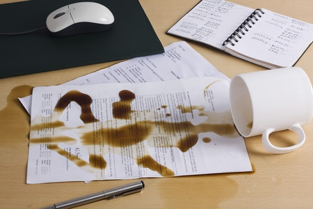 Spilt coffee over documents on a desk photo