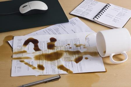 Spilt coffee over documents on a desk