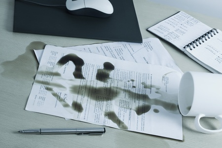 Spilt coffee over documents on a desk Stock Photo - 10238518