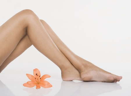 Womans leg with a lily flower photo