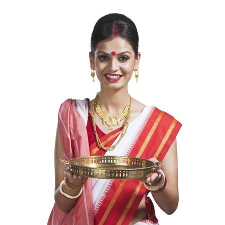 Traditional Bengali woman holding pooja thali photo