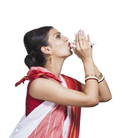 bengali: Traditional Bengali woman blowing shankha