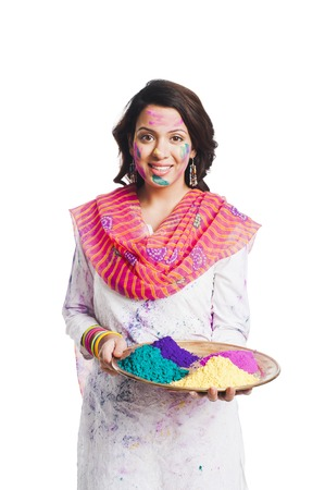 Woman holding Holi colors in a plate photo