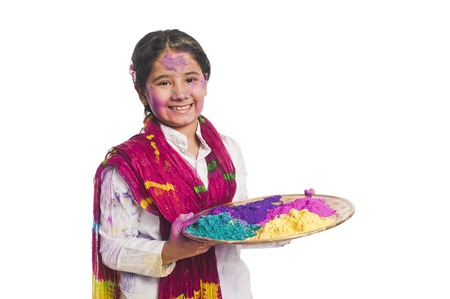 Girl holding Holi colors in a plate photo
