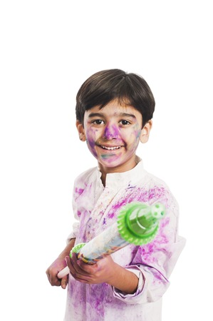 Boy celebrating Holi festival with pichkari Imagens