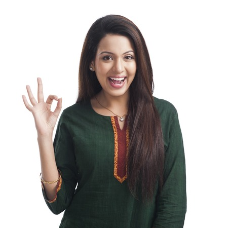 Portrait of a woman showing ok sign and smiling Imagens
