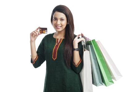 Portrait of a happy woman holding shopping bags and credit card photo