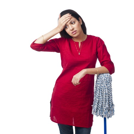 Woman leaning on a mop and suffering from a headache