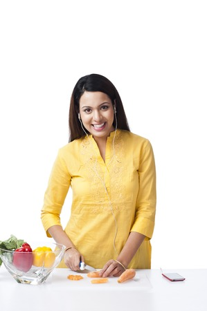 Woman cutting vegetables and listening music with an mp3 player Stock Photo