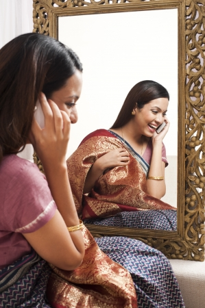 reflection: Reflection of a woman in mirror trying a sari on herself and talking on a mobile phone