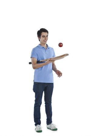 cricket bat: Man tossing a ball with a cricket bat