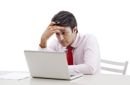 Businessman looking sad while working on a laptop photo