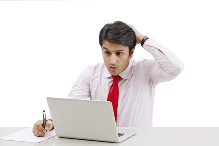 Businessman using a laptop and looking shocked photo