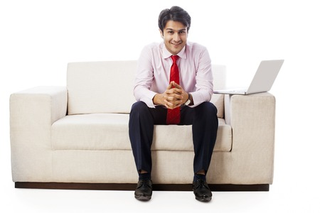 couch: Portrait of a businessman sitting on a couch and smiling Stock Photo