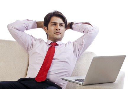 Businessman sitting on a couch and looking thinking in front of a laptop photo