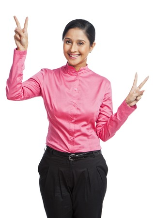 Portrait of a businesswoman gesturing victory sign photo