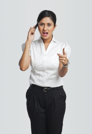 Businesswoman talking on a mobile phone and pointing photo