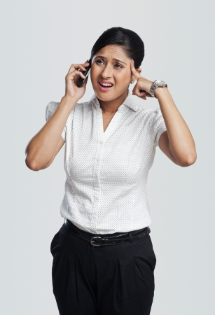 Businesswoman looking upset while talking on a mobile phone photo