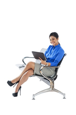 Businesswoman sitting on a bench and using a digital tablet photo
