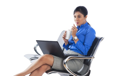 Businesswoman drinking soft drink while using a laptop photo