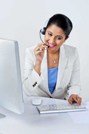 Female customer service representative using a desktop pc photo