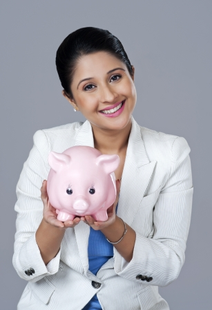 Portrait of a businesswoman holding a piggy bank photo