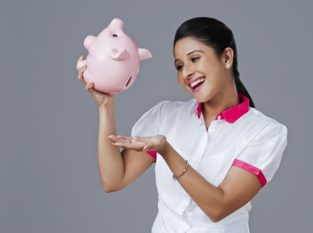 Woman withdrawing money from piggy bank photo