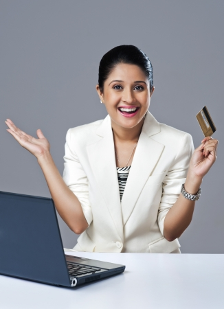 Businesswoman looking excited while doing online shopping with a laptop photo