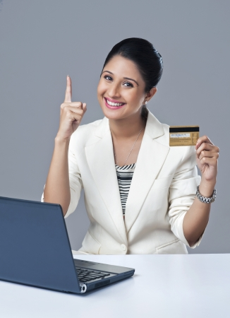 Portrait of a businesswoman holding a credit card and gesturing photo