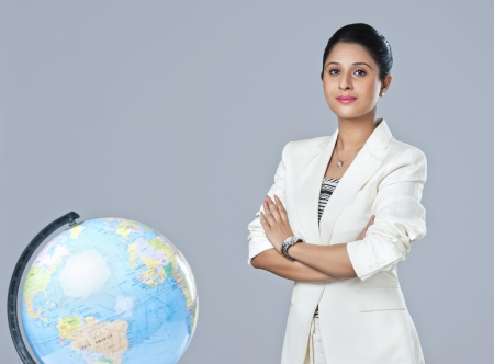 Portrait of a businesswoman standing next to a globe with her arms crossed photo