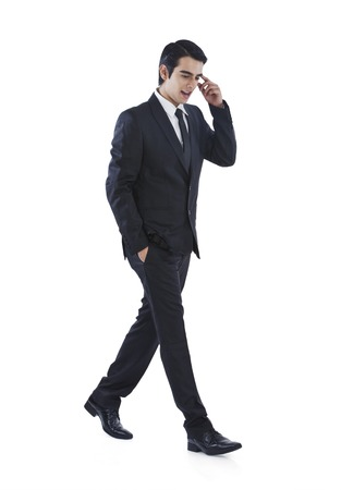 Businessman walking with his hands in pockets and thinking photo
