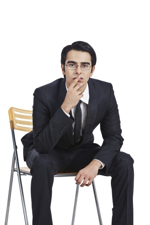 Businessman sitting on a chair and thinking photo