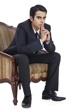 Businessman sitting in an armchair and thinking photo