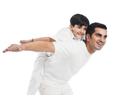 Gelukkige jongen rijden meeliften op zijn vader Stockfoto