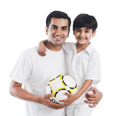 Portret van een gelukkige vader en zoon met voetbal Stockfoto