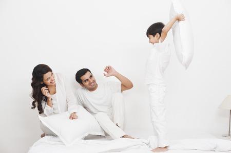 Gelukkige jongen kussengevecht met zijn ouders op het bed Stockfoto