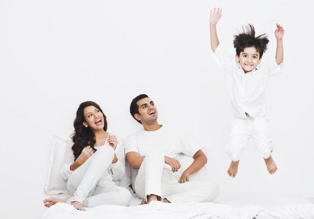 Gelukkige jongen springen op het bed met zijn ouders Stockfoto