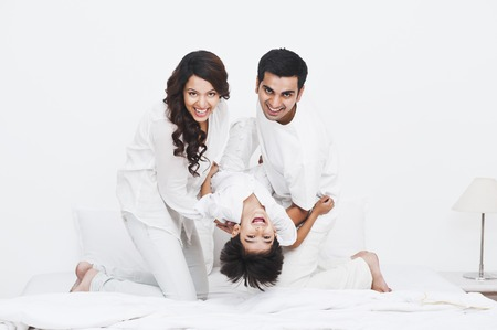 Happy parents playing with their son on the bed photo
