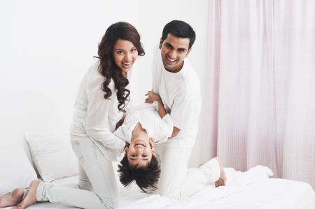 침대에 자신의 아들과 함께 행복한 부모 스톡 콘텐츠