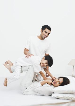 Gelukkige ouders spelen met hun zoon op het bed Stockfoto